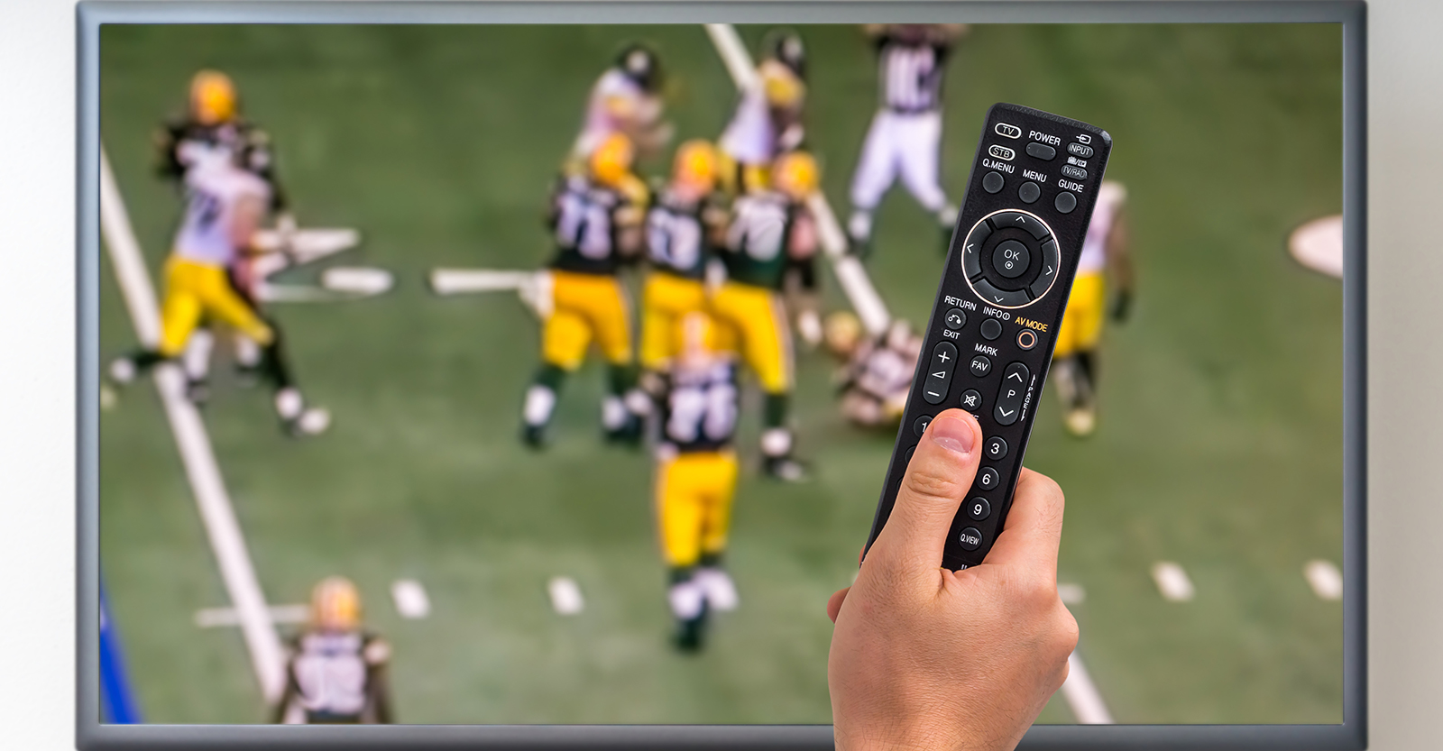 Man holding TV remote with football on in the background