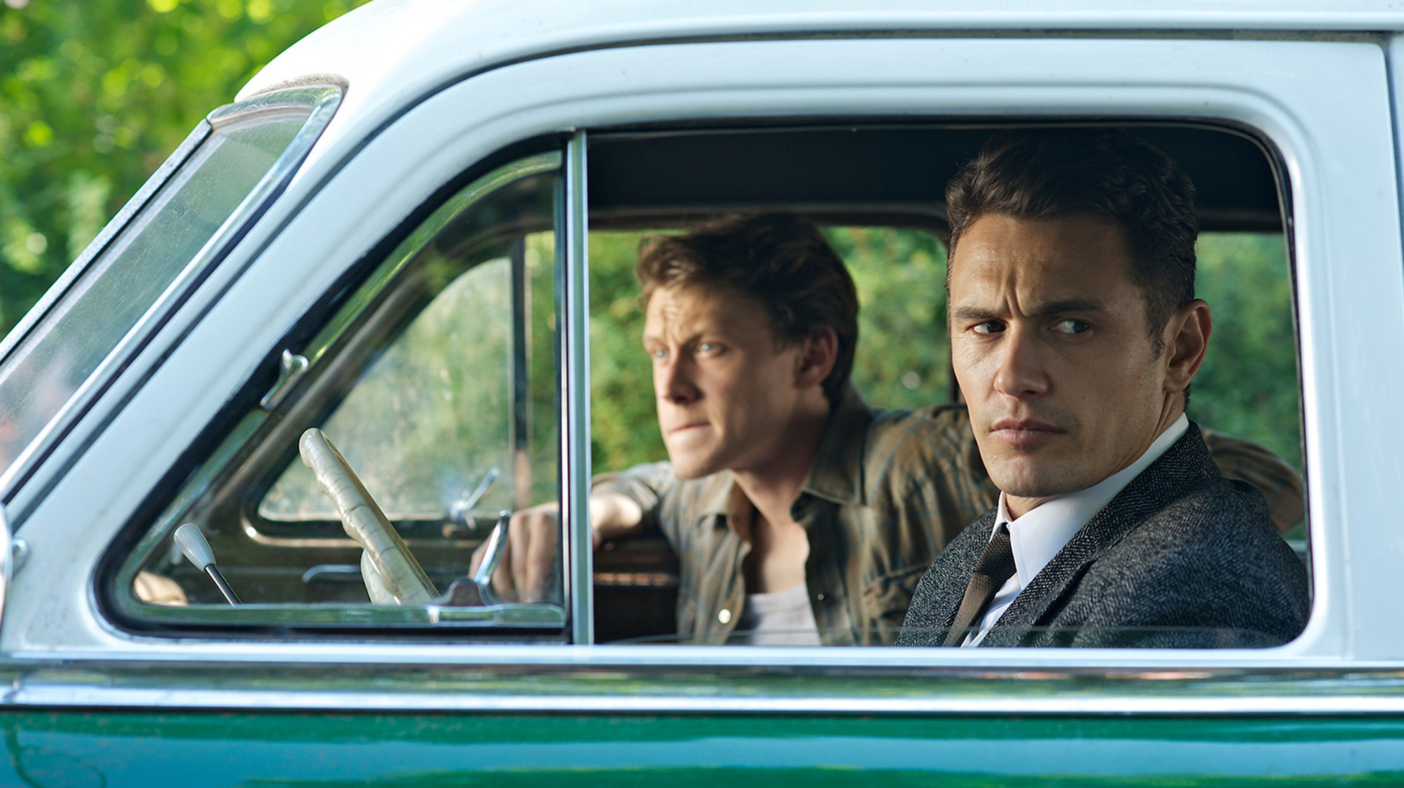 2 men driving in old blue truck