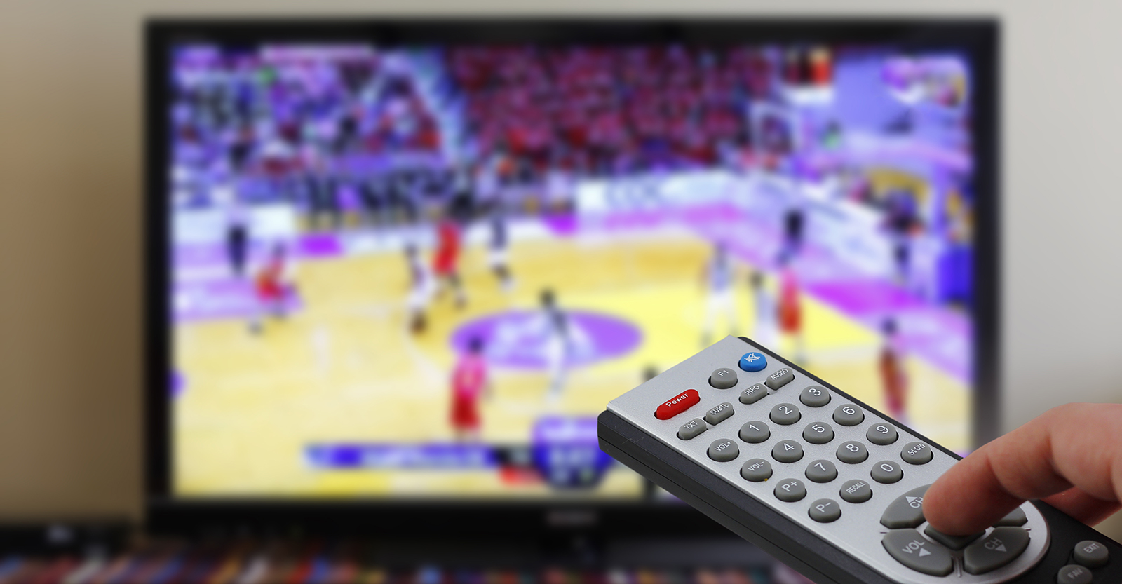 Man using remote control with the basketball game