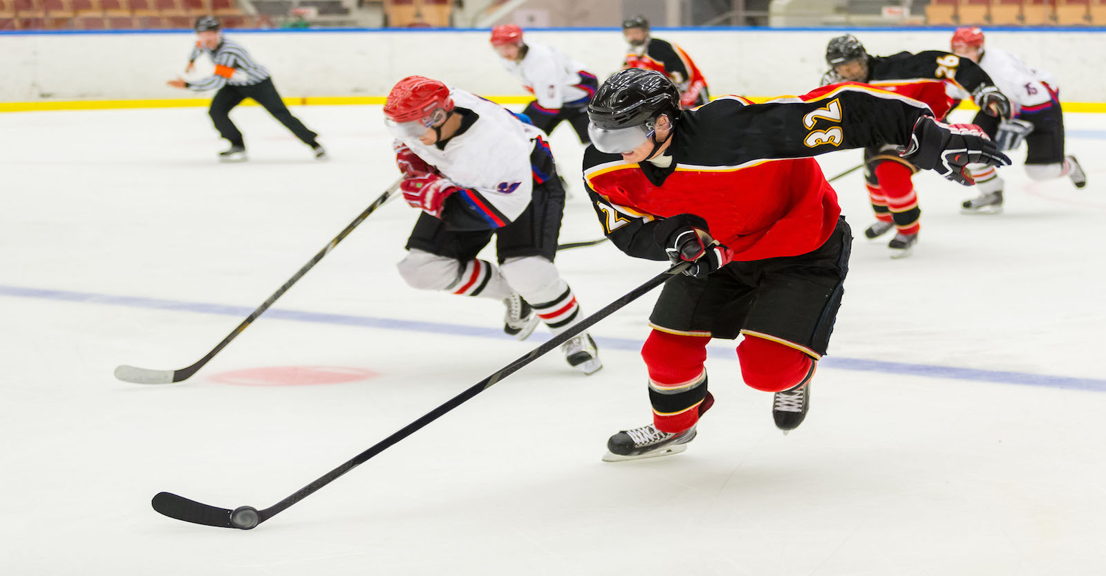 Hockey players racing to the puck