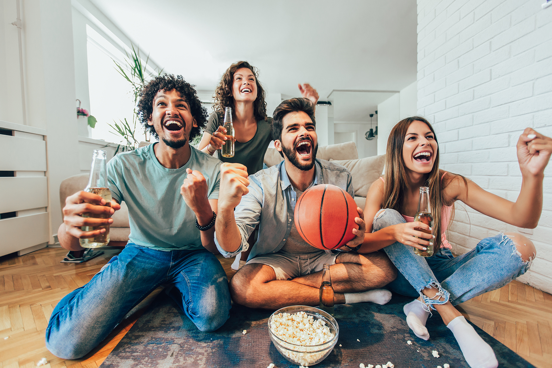 group of friends watching the basketball game with extreme excitement while eating and drinking