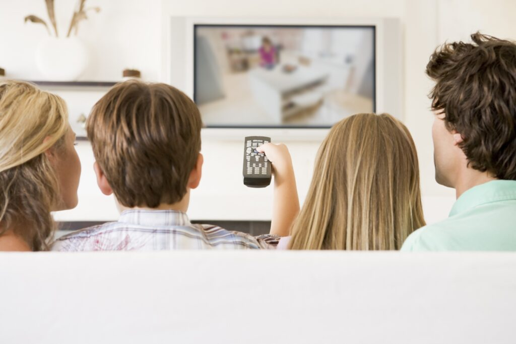 family watching TV while son holds the remote to change channels