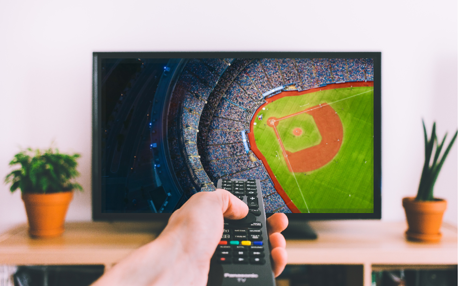man holding a remote control while watching the baseball game